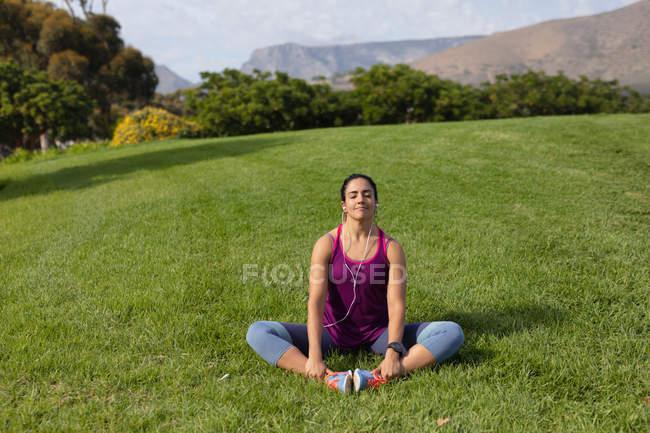 Vista frontal de una joven mujer caucásica con ropa deportiva sentada en la hierba, sosteniendo sus pies, estirando y escuchando música mientras hace ejercicio en un parque - foto de stock