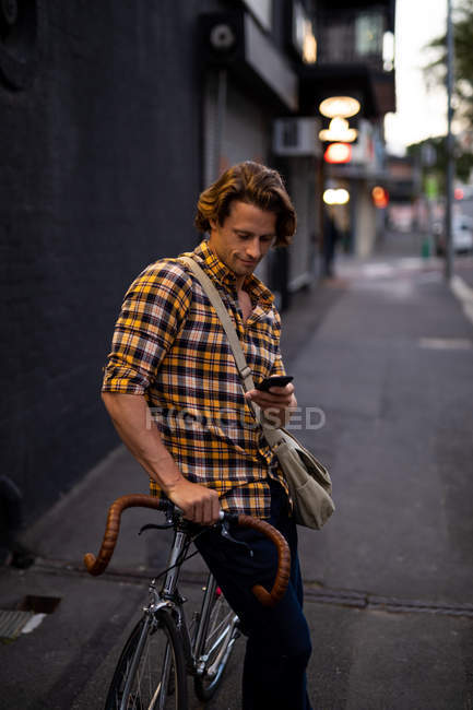 Side view close up of a young Caucasian man leaning on a bike and using a smartphone standing in a city street in the evening — Stock Photo