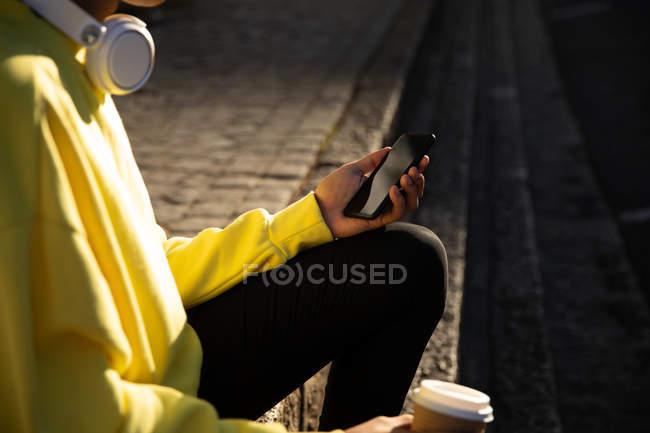 Vista laterale a metà sezione di un uomo alla moda in strada, che tiene uno smartphone e una tazza di caffè — Foto stock