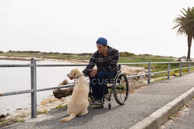 Вид на молоду Кавказьку людину в інвалідному візку, гуляючи з собакою в сільській місцевості біля моря — стокове фото