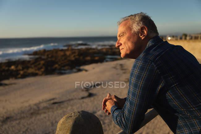 Vue latérale de près d'un homme caucasien mature admirant la vue sur la mer au coucher du soleil — Photo de stock