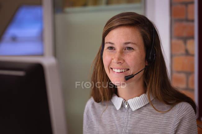 Vista frontal close-up de uma jovem mulher branca sorridente sentada em uma mesa trabalhando no escritório de uma empresa criativa usando um computador e usando um fone de ouvido — Fotografia de Stock