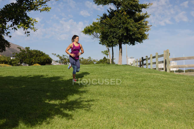 Front view of a young Caucasian woman wearing sports clothes running on grass and listening to music on earphones while working out on a sunny day in a park — Stock Photo