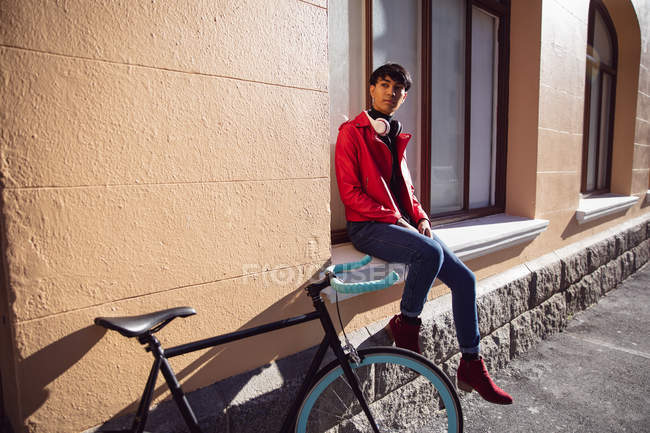 Front view of a fashionable young mixed race transgender adult in the street, sitting on a window sill next to a bike — Stock Photo