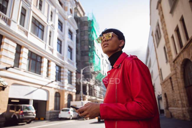 Vue latérale d'un jeune transgenre mixte à la mode adulte dans la rue, tenant un smartphone — Photo de stock