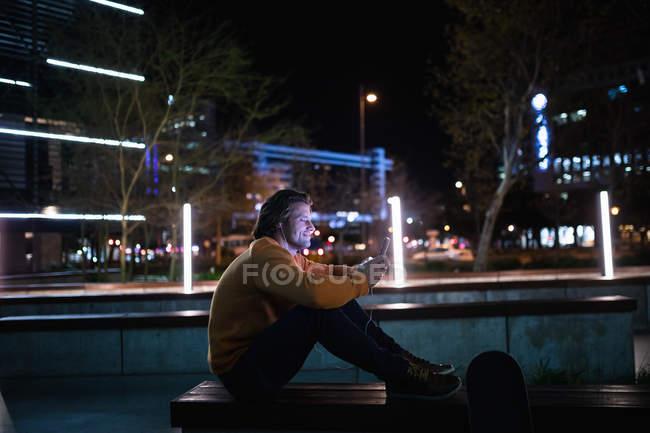 Vista lateral de um jovem caucasiano sentado em uma parede na rua à noite falando ao telefone com fones de ouvido, com um skate ao lado dele — Fotografia de Stock