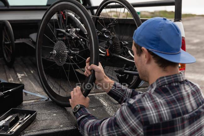 Заднього огляду крупним планом молодого Кавказького людини в інвалідному візку приймаючи лежачий велосипед з задньої частини своєї машини, щоб зібрати його — стокове фото