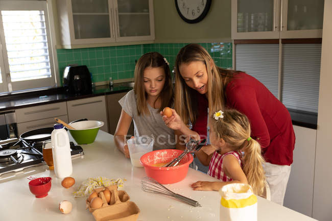 Front view of a young Caucasian woman cooking with her tween and younger daughters in their kitchen — стокове фото