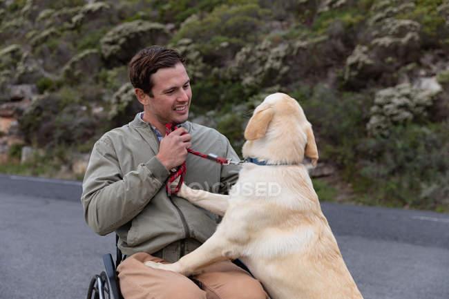 Вид спереди на молодого кавказца в инвалидном кресле, гуляющего со своей собакой в деревне, улыбающегося собаке, которая стоит на задних лапах — стоковое фото