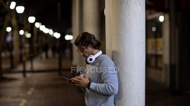 Vista lateral de un joven caucásico parado en una calle por la noche con auriculares, usando un teléfono inteligente y sosteniendo un café para llevar - foto de stock