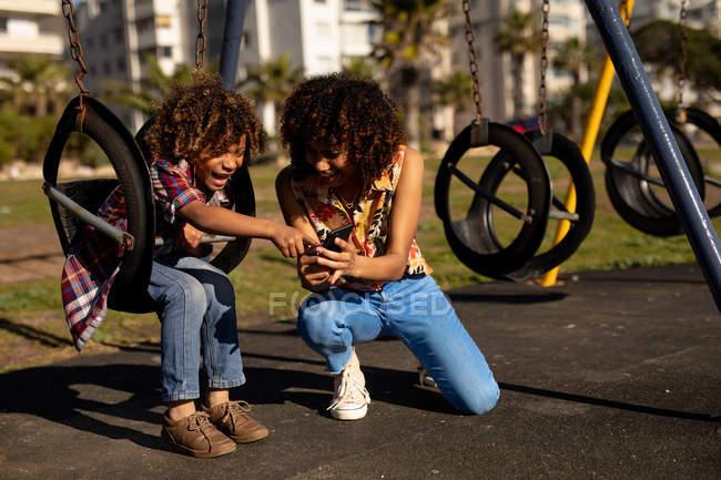 Vista frontale di una giovane donna da corsa mista e suo figlio pre-adolescente godendo tempo insieme giocare in un parco giochi, utilizzando uno smartphone su altalene in una giornata di sole — Foto stock