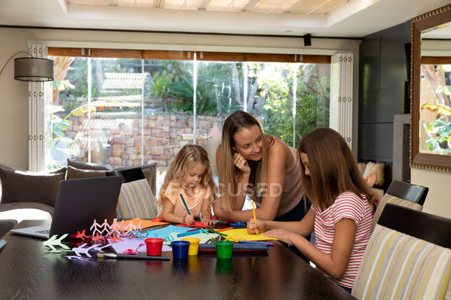 Front view of a young Caucasian pregnant woman doing crafts with her tween and younger daughters in their sitting room — Stock Photo