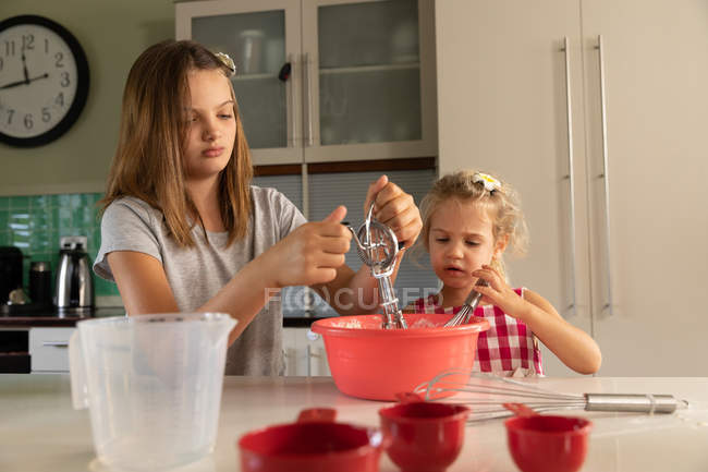 Front view of a tween Caucasian girl and her younger sister mixing food in a bowl cooking together in the kitchen — Stock Photo