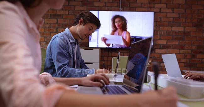 Vista laterale da vicino di una giovane donna e un uomo caucasico che lavorano nell'ufficio di un'azienda creativa. Una collega donna è visibile su uno schermo a parete, comunicante tramite collegamento video — Foto stock