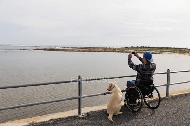 Заднього виду молодого Кавказького чоловіка в інвалідному візку приймаючи прогулянку зі своєю собакою біля моря, приймаючи фотографію — стокове фото