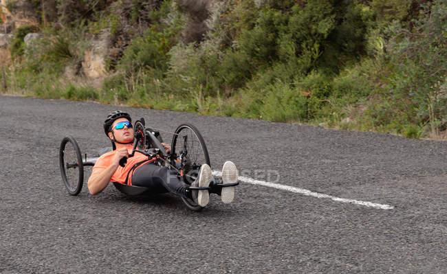 Вид збоку молодого Кавказького чоловіка в спортивному одязі на лежачому велосипеді по дорозі, з зеленню у фоновому режимі — стокове фото