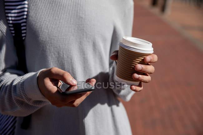 Вид спереди среднего сектора модного мужчины на улице, текстурирующего на смартфоне и держащего в руках чашку кофе — стоковое фото