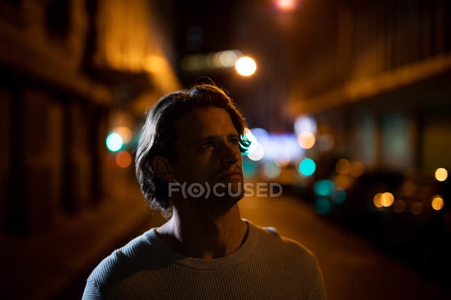 Close up front view of a young Caucasian man standing in a street at night, looking away — Stock Photo