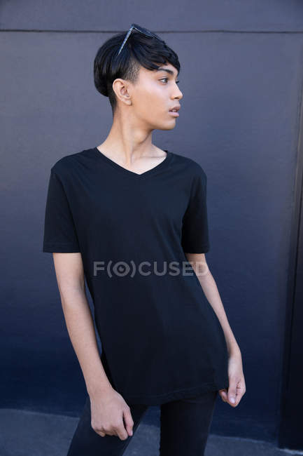 Side view of a fashionable young mixed race transgender adult in the street against a grey wall — Stock Photo