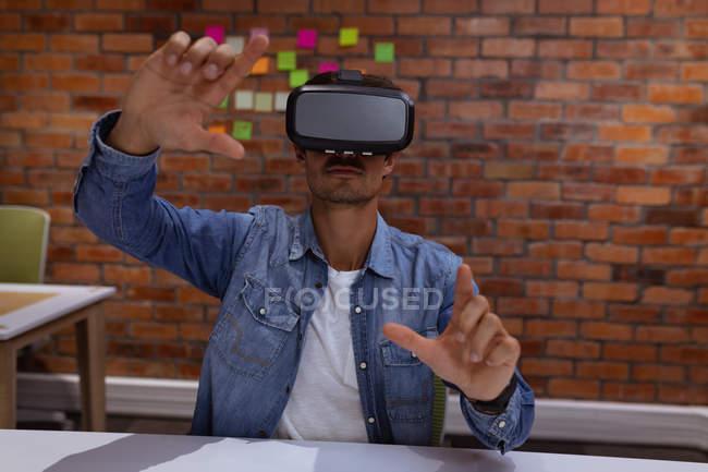 Vista frontal de cerca de un joven caucásico sentado en un escritorio con un casco VR con las manos levantadas, en la oficina de un negocio creativo - foto de stock