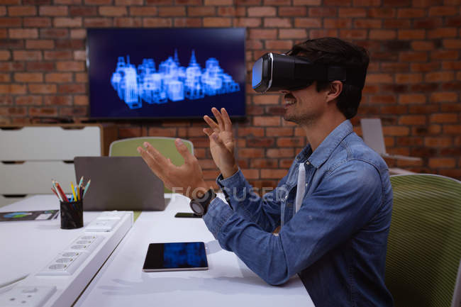 Side view close up of a young Caucasian man sitting at a desk wearing a VR headset with his hands raised, in the office of a creative business — Stock Photo
