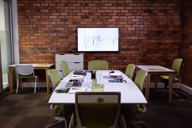 Vista do escritório moderno de um negócio criativo, com uma mesa de reunião, mesas, cadeiras e um monitor montado em uma parede de tijolos expostos — Fotografia de Stock