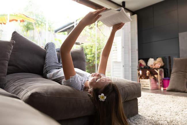 Seitenansicht Nahaufnahme eines kaukasischen Mädchens, das auf dem Rücken auf einem Stuhl liegt und in ihrem Wohnzimmer liest — Stockfoto
