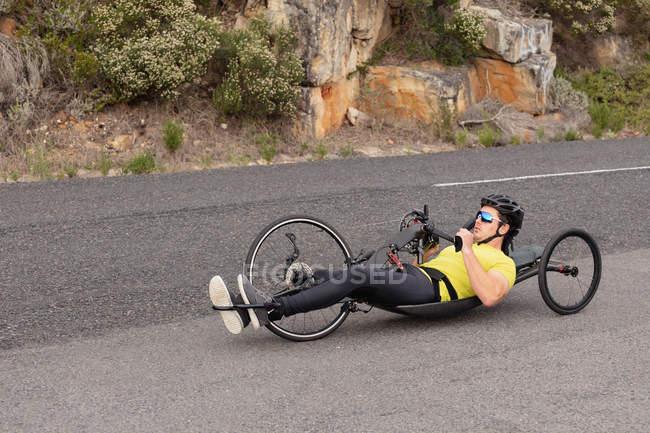 Вид збоку молодого Кавказького чоловіка в спортивному одязі на лежачому велосипеді по дорозі на дорогу, з скелями на задньому плані — стокове фото