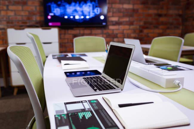 Vista lateral fechar de um computador portátil aberto na mesa no escritório de um negócio criativo, com um monitor montado em uma parede de tijolos expostos no fundo — Fotografia de Stock