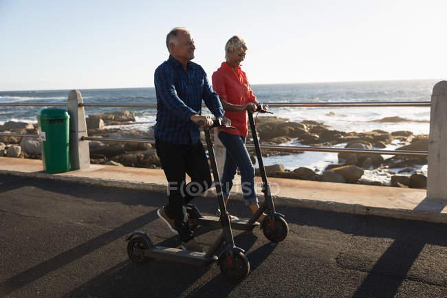 Opinião lateral uma equitação caucasiano madura do homem e da mulher e scooters pelo mar no por do sol — Fotografia de Stock