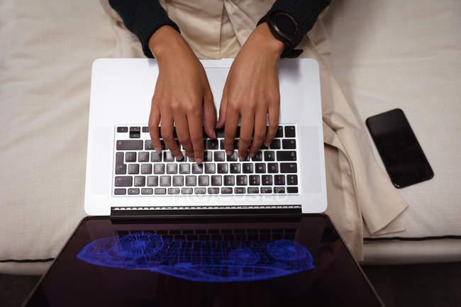 Vista frontal sección media de la mujer sentada en una sala de estar trabajando en el ordenador portátil en la oficina de un negocio creativo, un teléfono inteligente a su lado - foto de stock