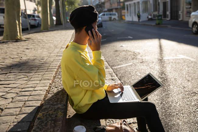 Вид сбоку на модную молодую смешанную расу трансгендерного взрослого на улице, используя ноутбук и разговаривая на смартфоне — стоковое фото