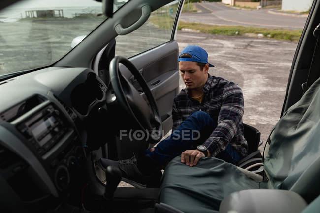 Вид спереду крупним планом молодого Кавказького чоловіка вихід з машини в інвалідному візку на автостоянці в сільській місцевості — стокове фото