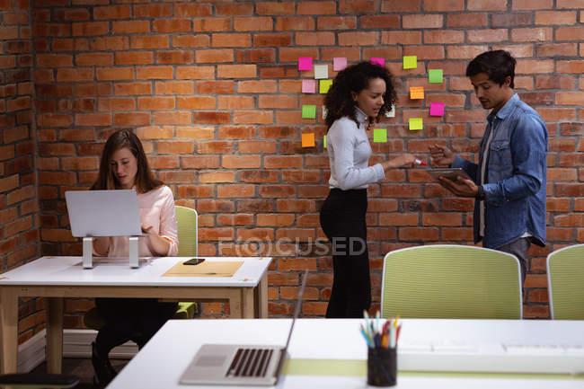 Vista lateral de una joven mujer de raza mixta y un joven hombre caucásico de pie mirando una tableta y una lluvia de ideas en la oficina de un negocio creativo, mientras una joven colega caucásica se sienta en un escritorio trabajando en una computadora portátil - foto de stock