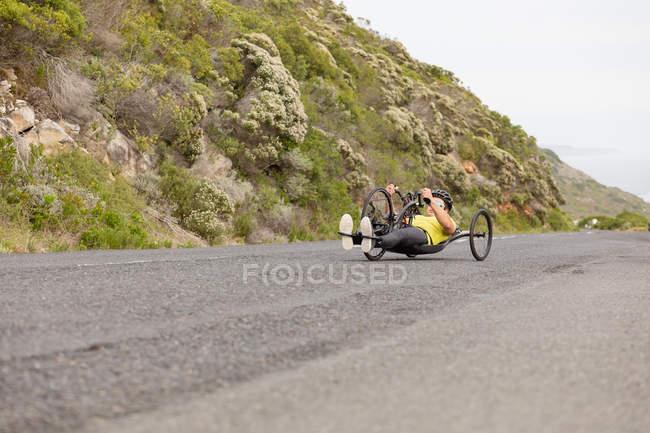 Вид на молоду Кавказьку людину в спортивному одязі на лежачому велосипеді по дорозі, з зеленню у фоновому режимі — стокове фото