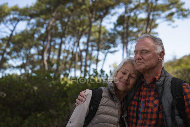 Front view close up of a mature Caucasian man and woman embracing with eyes closed during a walk in a rural setting — Stock Photo