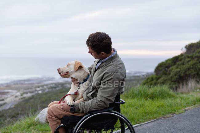 Вид збоку молодого Кавказького чоловіка в інвалідному візку приймаючи прогулянку зі своєю собакою в сільській місцевості біля моря, гладить собаку на коліна — стокове фото