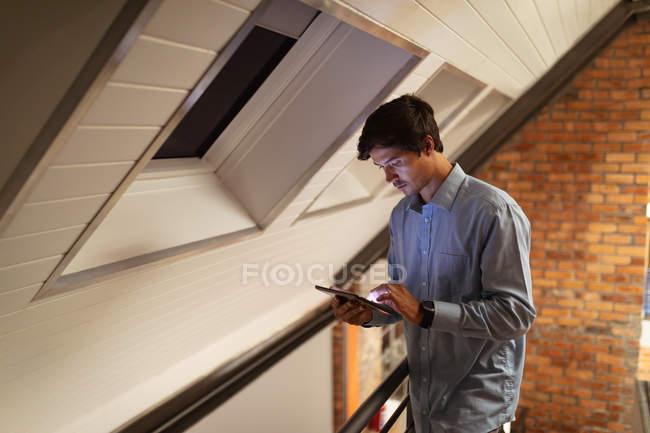 Зворотний бік зображення молодого кавказького чоловіка, який стоїть в офісі творчого бізнесу, дивлячись на планшетний комп'ютер вночі. — стокове фото