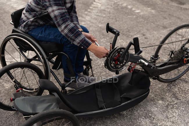 Низький розділ людини в інвалідному візку складання лежачого велосипеда в автостоянці — стокове фото