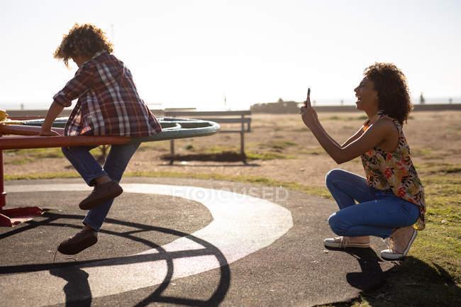 Vista laterale di una giovane donna di razza mista e suo figlio pre-adolescente godendo tempo insieme giocare in un parco giochi in terra, seduto su una giostra e scattare foto in una giornata di sole — Foto stock