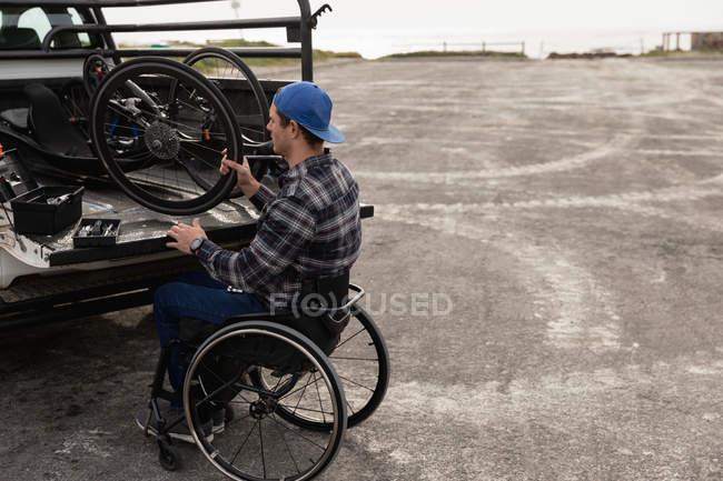Вид збоку молодого Кавказького чоловіка в інвалідному візку приймаючи лежачий велосипед з задньої частини своєї машини, щоб зібрати його на автостоянці біля моря — стокове фото