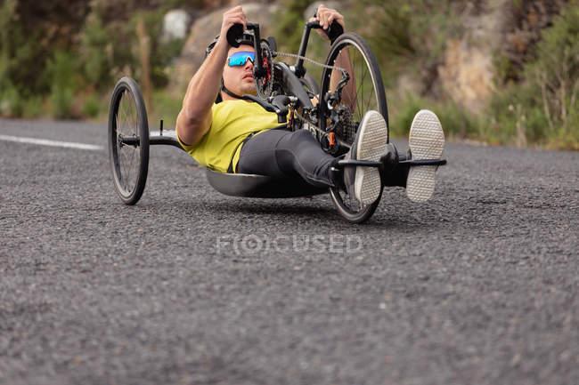 Вид на молоду Кавказьку людину в спортивному одязі на лежачому велосипеді велоспорту на заміському шляху — стокове фото