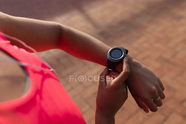 Over the shoulder view of woman wearing sports clothes checking her smartwatch and listening to music on earphones while working out on a sunny day in a park — Stock Photo