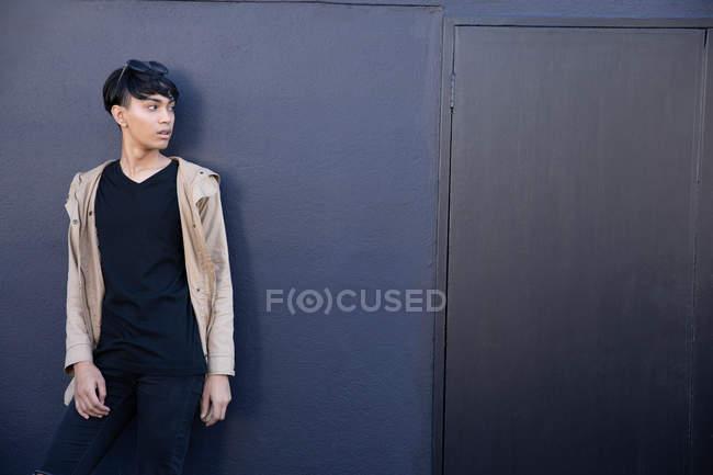 Vista lateral de um jovem elegante mestiço transexual adulto na rua contra uma parede cinza — Fotografia de Stock