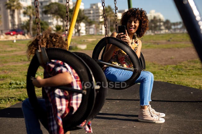 Vista frontale di una giovane donna di razza mista e suo figlio pre-adolescente godendo tempo insieme giocare in un parco giochi, scattare foto su altalene in una giornata di sole — Foto stock