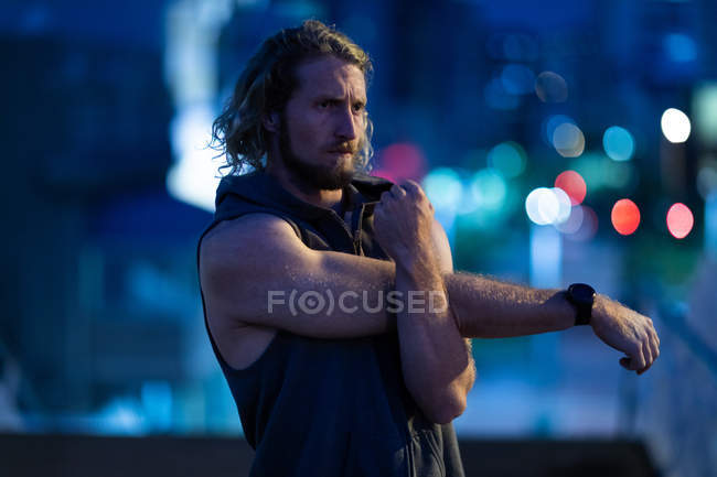 Front view of a young athletic Caucasian man exercising in a city park in the evening, stretching his arms with defocused city lights in the background — Stock Photo
