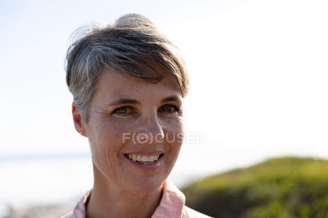 Portrait close up of a middle-aged caucasian woman with short grey hair enjoying free time relaxing beside the sea smiling to camera — стокове фото