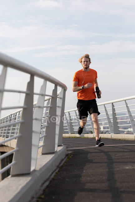 Front view of a young athletic Caucasian man exercising on a footbridge in a city, running with earphones on and holding a bottle — Stock Photo