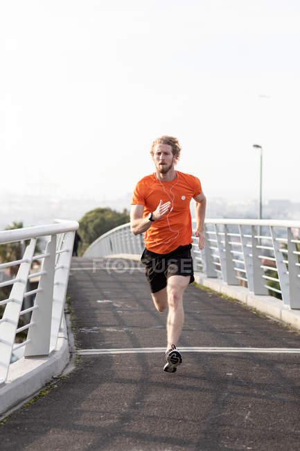 Вид спереди на молодого атлета-кавказца, тренирующегося на пешеходном мосту в городе, бегущего и слушающего музыку в наушниках — стоковое фото