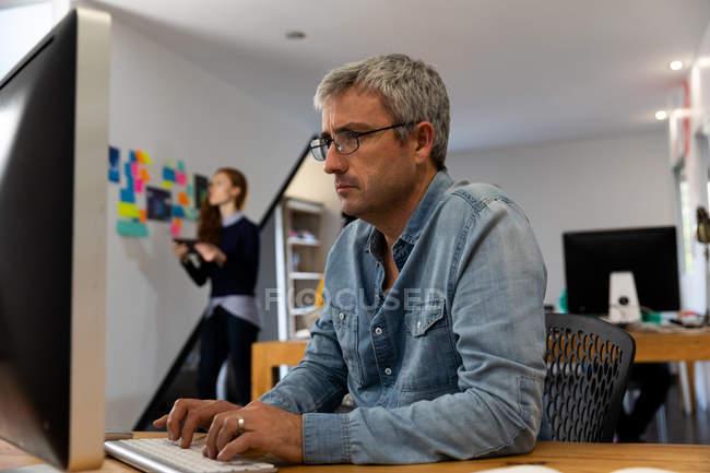 Vista lateral de un hombre caucásico trabajando en un escritorio usando una computadora en una oficina creativa, usando gafas y camisa de mezclilla con su colega femenina en el fondo . - foto de stock